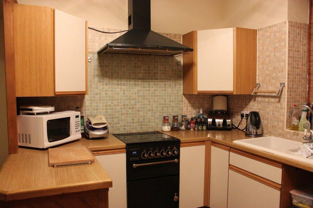 Uma cozinha com armários e um micro-ondas